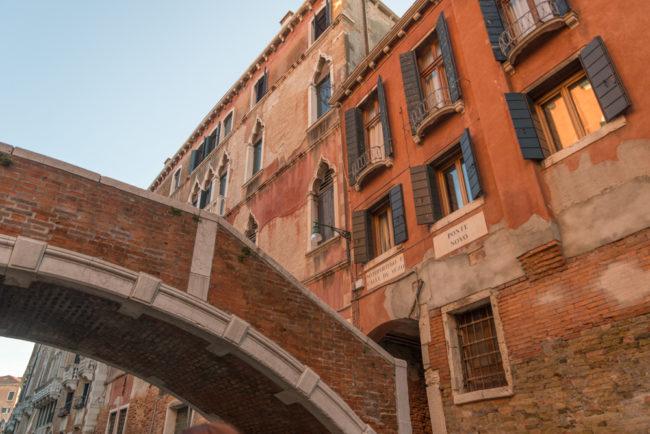 Venedig, Italien, stiller Kanal mit Brücke und roter Hausfassade